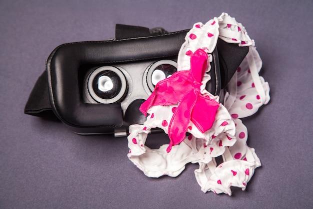 상단에 활이 있는 점선 분홍색 흰색 란제리가 있는 모바일 장치용 가상 현실 안경