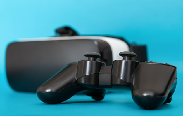 Virtual reality glasses and a joystick on a blue surface