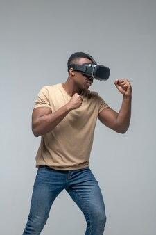 가상 현실, 안경. 회색 배경에 격리된 주먹으로 움직이는 vr 안경을 쓴 근육질의 어두운 피부 남자