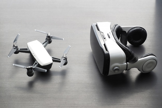 Virtual reality glasses and small drone on dark wooden table.
