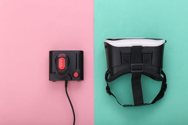 Гарнитура виртуальной реальности и ретро джойстик на розово-голубом пастельном фоне. развлечения, видеоигры. вид сверху