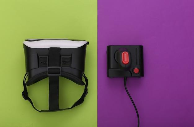 Гарнитура виртуальной реальности и ретро джойстик на пурпурно-зеленом фоне. развлечения, видеоигры. вид сверху