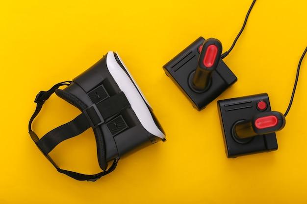 Гарнитура виртуальной реальности и ретро-джойстики на желтом фоне. развлечения, видеоигры. вид сверху
