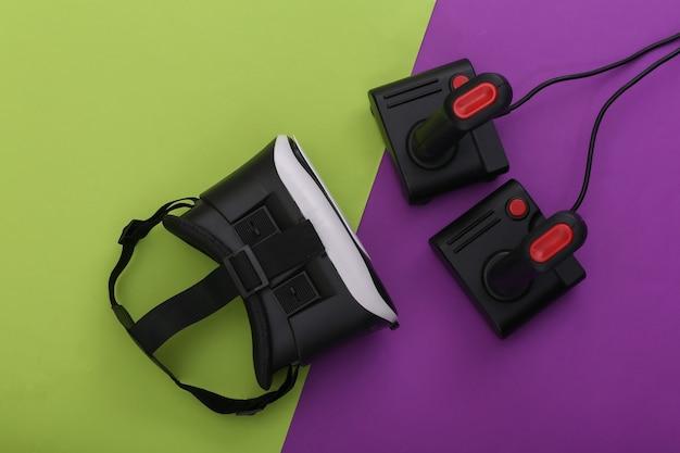 Гарнитура виртуальной реальности и ретро джойстики на пурпурно-зеленом фоне. развлечения, видеоигры. вид сверху