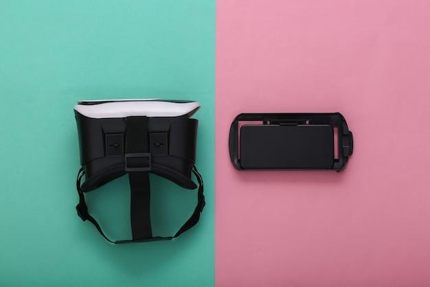 Гарнитура и смартфон виртуальной реальности на розово-голубом пастельном фоне. современные гаджеты. вид сверху