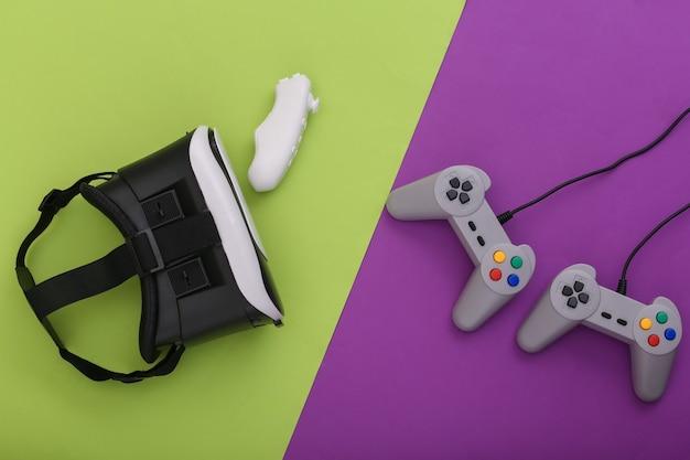 Гарнитура виртуальной реальности, современный и ретро джойстик и геймпады на пурпурно-зеленом фоне. развлечения, 3d видеоигры. вид сверху