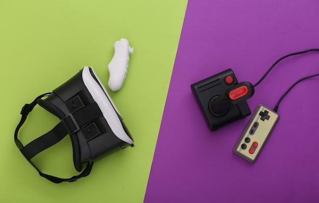 Гарнитура виртуальной реальности, современные и ретро-джойстики и геймпады на фиолетово-зеленом фоне. развлечения, видеоигры. вид сверху