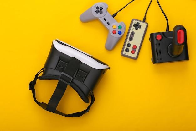 Гарнитура виртуальной реальности, ретро-геймпады и джойстик на желтом фоне. развлечения, 3d видеоигры. вид сверху