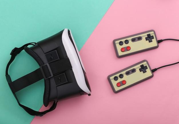 Гарнитура виртуальной реальности, ретро-геймпады на розово-голубом пастельном фоне. развлечения, 3d видеоигры. вид сверху