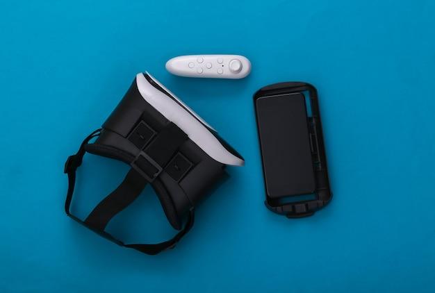 Гарнитура виртуальной реальности с джойстиком и смартфоном на синем фоне. современные гаджеты. вид сверху