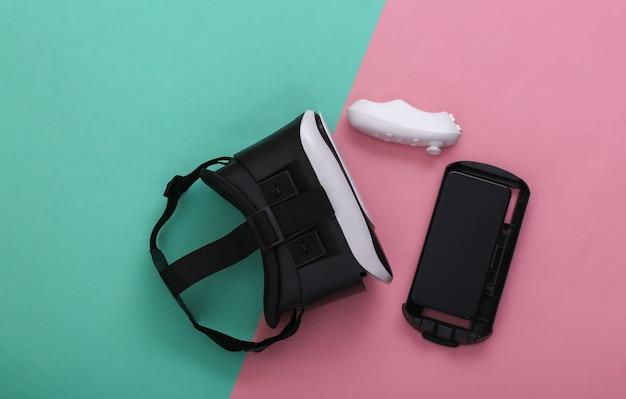 Гарнитура виртуальной реальности с джойстиком и смартфоном на розово-голубом пастельном фоне. современные гаджеты. вид сверху