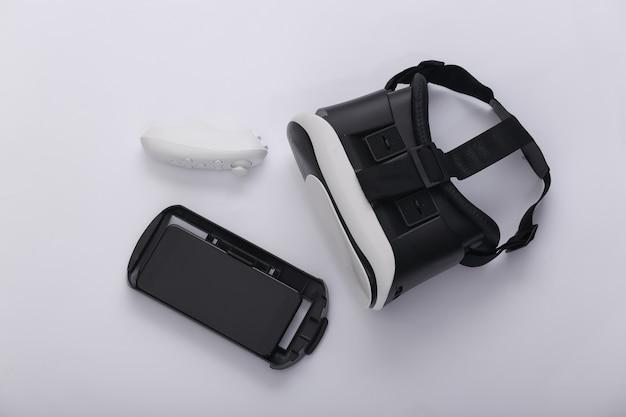 Гарнитура виртуальной реальности с джойстиком и смартфоном на белом фоне. современные гаджеты. вид сверху