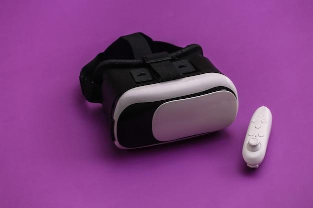 Гарнитура виртуальной реальности с джойстиком на фиолетовом фоне. современные гаджеты