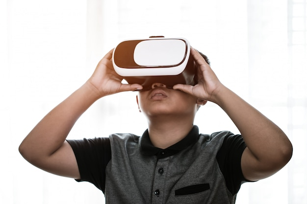 Virtual reality interaction headset by asian student wearing vr box over technology digital hud screen