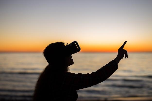 가상 현실이 여기 있습니다. 아름다운 열대 해변에서 가상 현실 안경을 사용하는 젊은 남자
