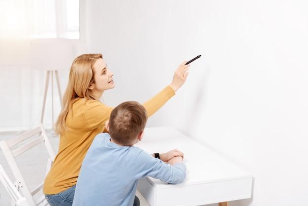 仮想画面。彼女の息子と一緒に座って、新しい技術について彼に教えながら壁を指してうれしそうな賢い若い女性