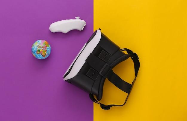 Виртуальное путешествие. гарнитура виртуальной реальности с глобусом, джойстиком на желтом фиолетовом фоне. вид сверху