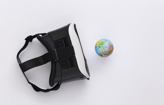Виртуальное путешествие. гарнитура виртуальной реальности с глобусом на белом фоне. вид сверху