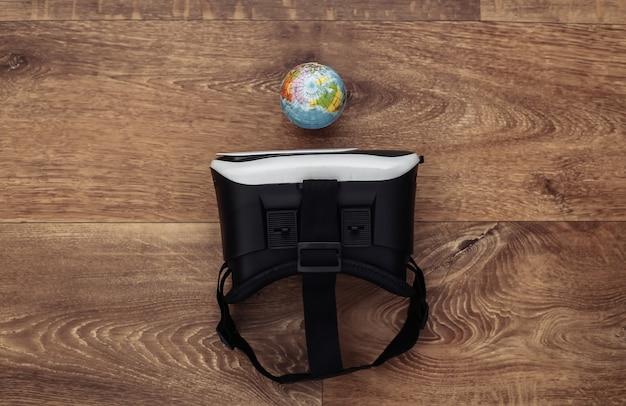 Виртуальное путешествие. гарнитура виртуальной реальности с глобусом на деревянных фоне. вид сверху