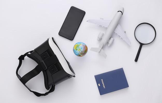 Виртуальное путешествие. гарнитура виртуальной реальности с глобусом, паспортом, смартфоном и самолетом на белом фоне. вид сверху