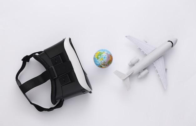 Виртуальное путешествие. гарнитура виртуальной реальности с глобусом, самолетом на белой предпосылке. вид сверху