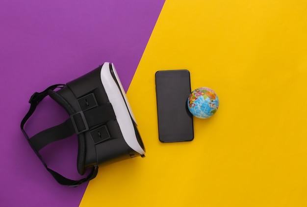 Виртуальное путешествие. гарнитура виртуальной реальности с глобусом, смартфон на желто-фиолетовом фоне. вид сверху