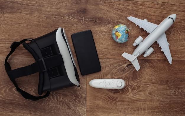 Виртуальное путешествие. гарнитура виртуальной реальности с джойстиком и смартфоном, глобусом и самолетом на деревянном фоне. вид сверху