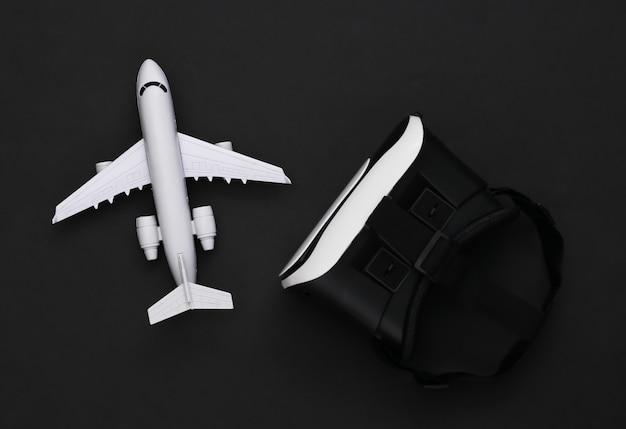 Виртуальное путешествие. гарнитура виртуальной реальности с самолетом на черном фоне. вид сверху
