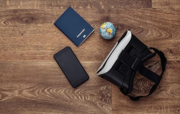 Виртуальное путешествие. гарнитура виртуальной реальности со смартфоном, глобусом и паспортом на деревянном фоне. вид сверху