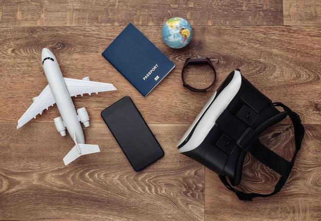 Виртуальное путешествие. гарнитура виртуальной реальности со смартфоном, глобусом, паспортом и самолетом на деревянном фоне. вид сверху