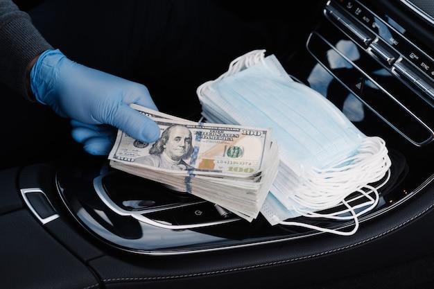 ウイルスの概念。ゴム手袋で手はドル紙幣のスタックを保持し、医療用マスクを販売し、車の中でポーズをとってお金を稼ぎます。 covidエピデミック。必要な製品の市場での推測。隔離期間