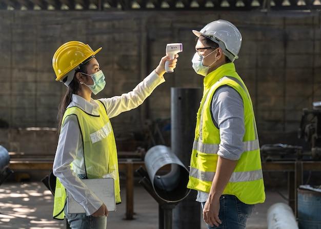 Virus covid 19危機のアジア人スタッフは、スキャンのために作業に入る前にデジタル体温計の訪問者が発熱をチェックし、コロナウイルスまたはcovid-19から保護します