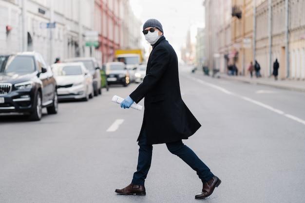 바이러스 코 비드 -19. 남자 검은 코트를 입은 도로 십자가