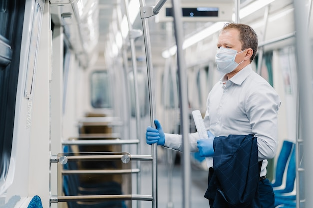 Virus hygiene and safety concept. serious man dressed in elegant outfit, disposable mask and rubber gloves, touches handrail in underground carriage, commutes to office during quarantine time