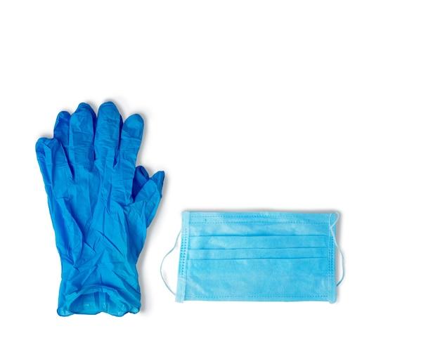 ウイルス対策の青いゴム手袋と白い表面の医療用マスク。