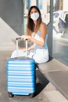 Защита от вирусов в общественном транспорте. женщина, путешествующая в защитной маске. концепция пандемии и загрязнения вируса. женщина ждет на вокзале.