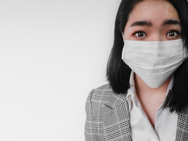 ウイルス恐怖アジアの女性は、白い壁に怖い探して身に着けているコロナウイルスマスク保護に衝撃を与えた