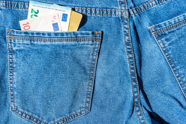 Пластиковая банковская карта visa с наличными евро в синих джинсах - концепция денег