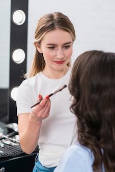 Visagiste making facial makeup to brunette model in studio