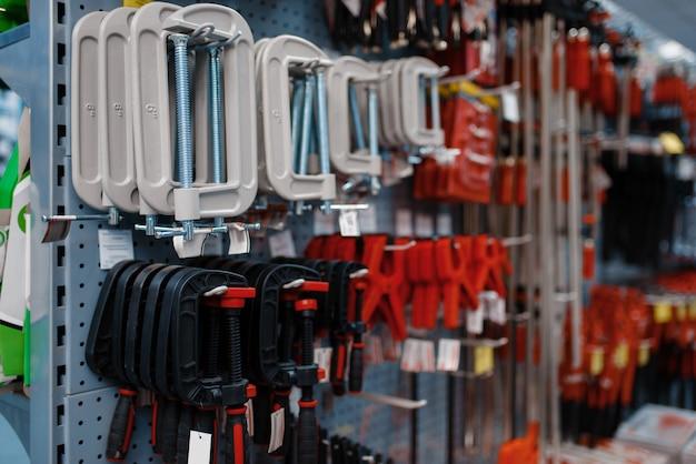 Тиски и зажимы на стойках в магазине инструментов крупным планом, никто. выбор оборудования в строительном магазине, профессиональный инструмент в супермаркете