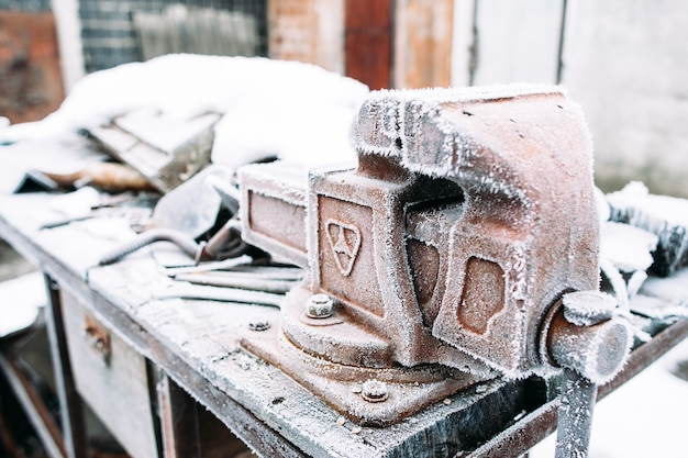눈으로 덮여 테이블에 바이스 스탠드. 겨울에 도구를 외부에 두었습니다. 추위, 초기 서리, 쉰, 재주꾼 개념