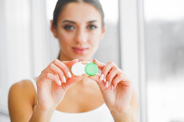 Концепция видения и медицины. молодая девушка держит глазные капли в руках. портрет красивой женщины с контактными линзами. здоровый взгляд