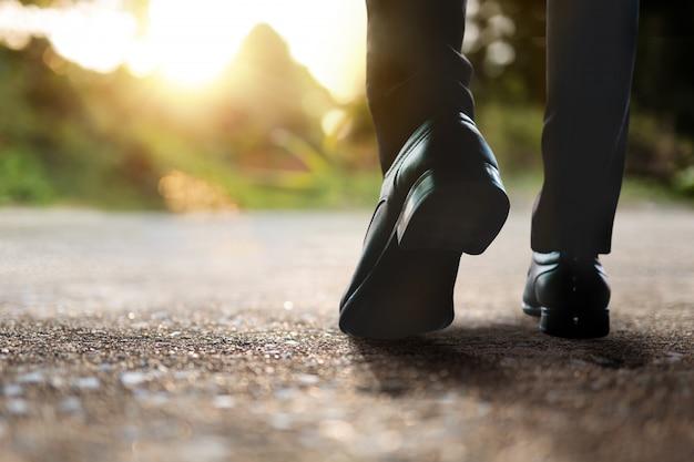 ビジョンと成功したコンセプト。キャリアへの挑戦。屋外を歩くビジネスマンの低いセクション。背景として自然光