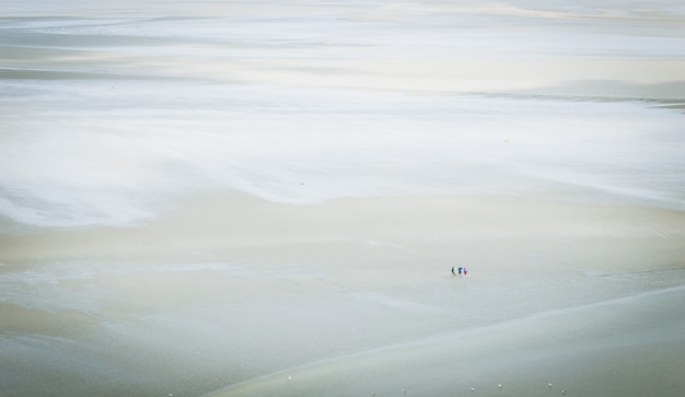 Vision of a group of tourists walking on the sand, in the mudflat.