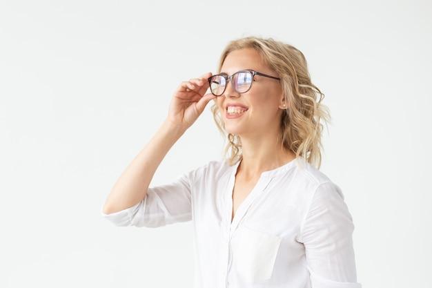 Зрение, оптика и красота - молодая блондинка надевает очки на белой стене.