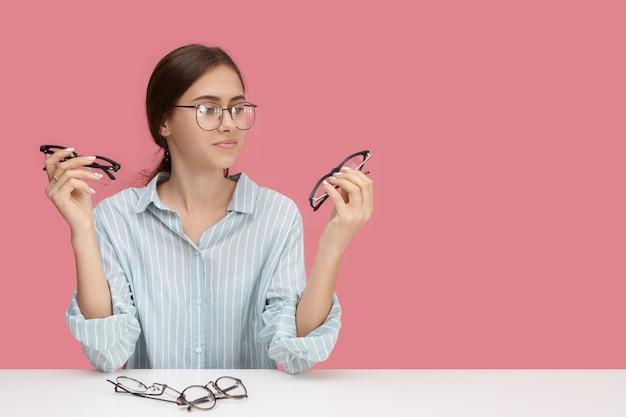 視覚、光学、視力、近視、人、アイウェアのコンセプト。スタイリッシュで美しい近視の若い女性が遠方眼鏡を選び、2組の眼鏡を持ち、優柔不断な表情をしている写真