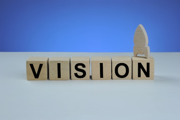 Vision word written on wood cube. with blue background. business concept