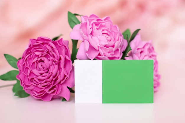 Visit card with place for text for florist on pink peonies flowers background