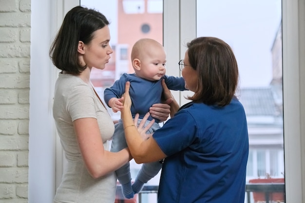 Visit of doctor pediatrician home, mother with baby son of seven months talking with doctor