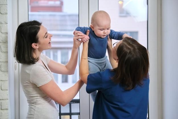 医師の小児科医の家の訪問、医師と話している7ヶ月の赤ん坊の息子を持つ母親。 1年までの子供の健康と育児の検査